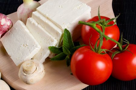 Slices of white cheese with tomato and mushrooms photo