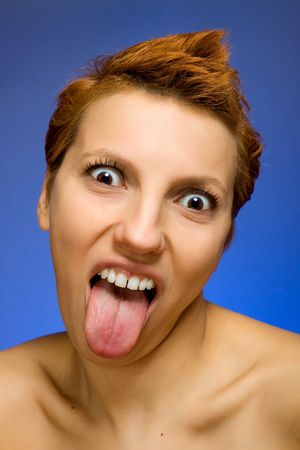 Portrait of beautiful woman showing her tongue out on blue background photo