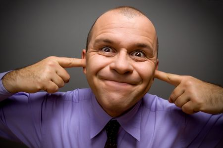 Silly adult man holding fingers in his ears photo