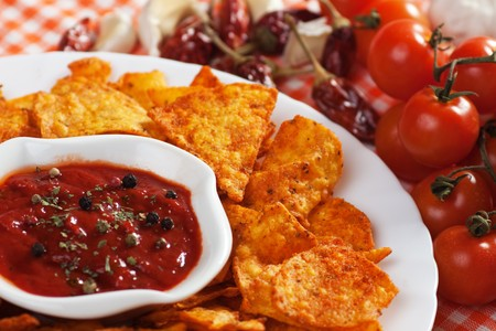 Tortilla chips with hot salsa dip, tomato and chili peppers photo