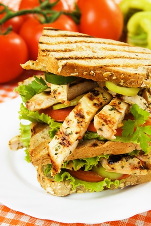 Grilled chicken sandwich with lettuce and tomato slices photo