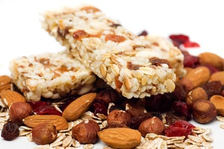 barra de cereal: Barra de granola con fruta seca y nueces sobre fondo blanco