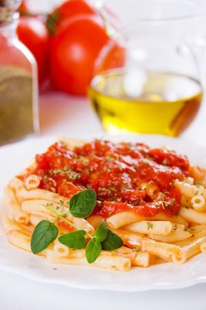 Traditional italian macaroni pasta with tomato sauce and oregano photo