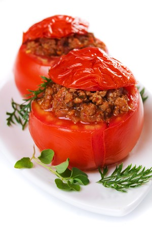 Baked tomato stuffed with ground beef isolated on white background photo
