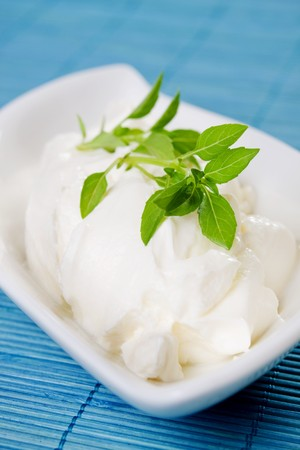 Sour milk cream in white bowl with basil leaves