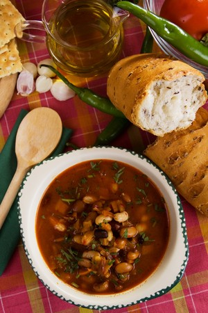 Kidney bean vegetable soup served with bread and hot peppers photo