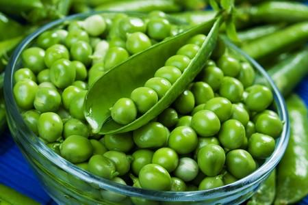 peas: Fresh raw green peas in glass bowl