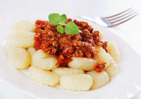 gnocchi: Gnocchi di patata, italian potato noodles with sauce bolognese Stock Photo