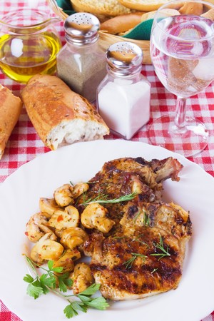 loin chops: Grilled pork loin chops served an white plate with mushrooms