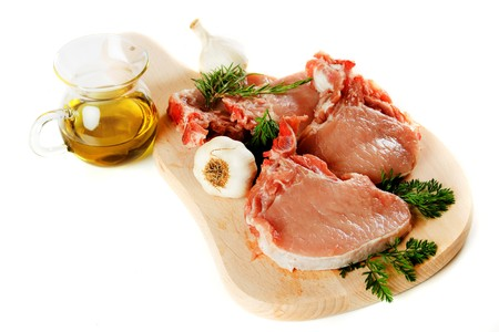 loin chops: Raw pork loin chops on chopping board isolated over white background