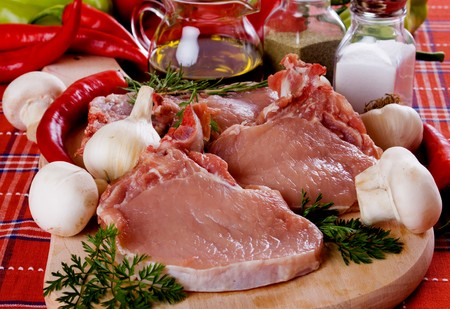 Raw pork loin chops with vegetables on chopping board
