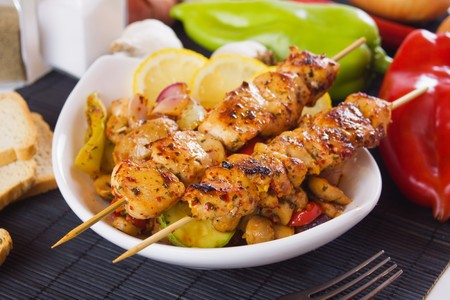 Grilled chicken meat kebab on skewer with vegetables photo
