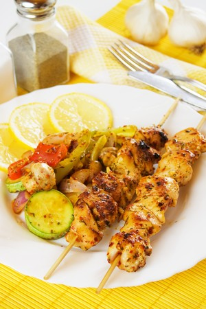 chicken meat: Grilled chicken meat kebab on skewer with vegetables and lemon slices