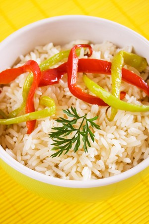 Cooked rice with slices of green and red bell pepper photo