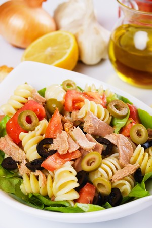 Delicious tuna salad with pasta, tomato and olives photo