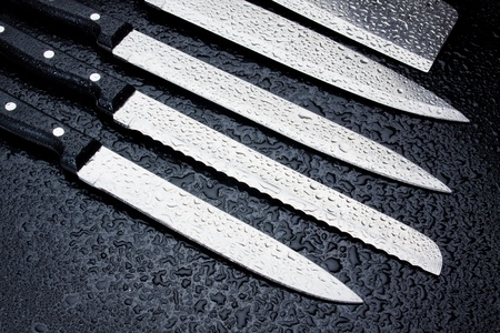 stainless steel kitchen: Set of stainless steel kitchen knives on wet background