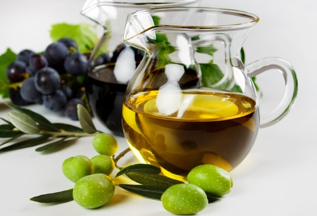 Aceite de oliva virgen y vinagre balsámico sobre fondo blanco Foto de archivo