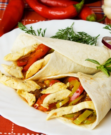 chicken meat: Taco shells with chicken meat and vegetables on white plate