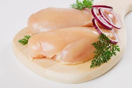 Raw chicken breast meat on wooden chopping board