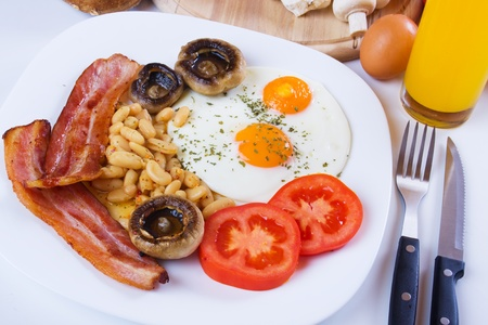 english breakfast: Fried eggs, bacon, beans and mushrooms served for healthy breakfast Stock Photo