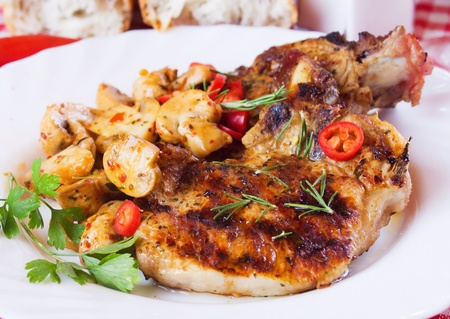 loin chops: Grilled pork loin chops served with mushrooms and chili peppers Stock Photo