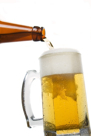 Beer bein poured from the bottle isolated on white photo