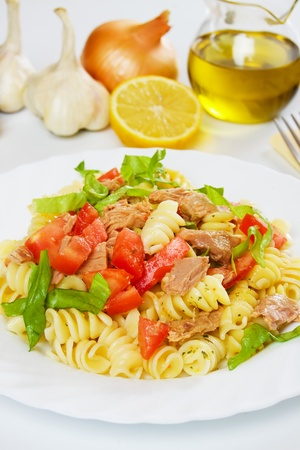 Tuna salad with pasta, tomato and lettuce on white plate photo