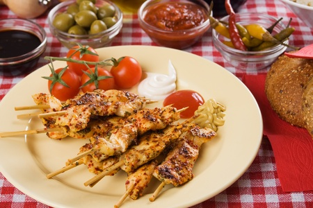 Barbecued chicken meat on skewer served as party food photo