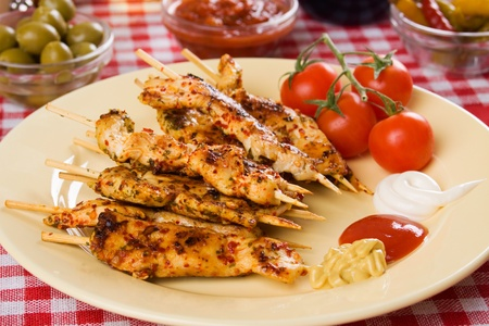 Grilled chicken white meat on skewer with mustard, ketchup an mayonnaise photo