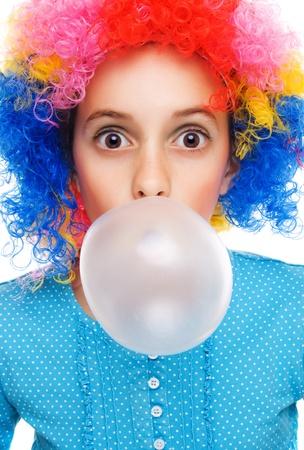 Junges Mädchen mit Clown Perücke und Bubble Gum isoliert auf weiss