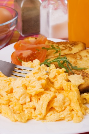 Scrambled eggs served with tomato and french toast for rich and healthy breakfast photo