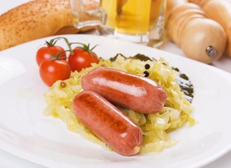 comida alemana: Chorizo frito y choucroute en plato blanco, comida tradicional de alem�n