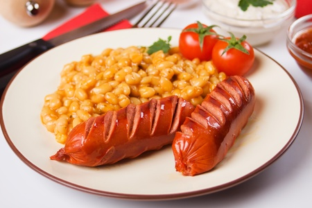 Fried sausages with white beans served with cherry tomato photo