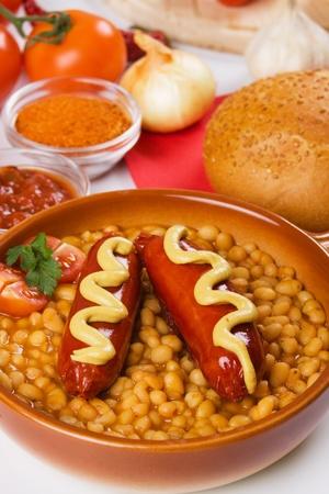 european food: Salchichas alemanas con frijoles blancos y mostaza, comida tradicional europea Foto de archivo