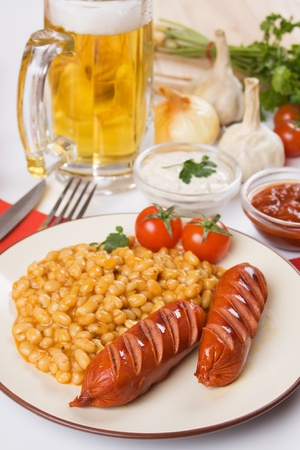 Fried sausage with cooked beans served with mug of beer Stockfoto - 8930635