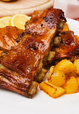 Delicious barbecued honey glazed ribs with baked potato photo