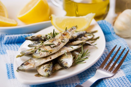Grilled sardine fish served with with rosemary and lemon photo