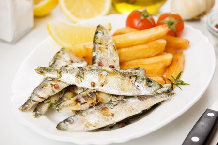 Grilled sardine fish served with french fries, tomato and lemon photo