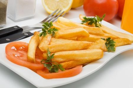 prepared potato: French fries, prepared potato served with fresh tomato Stock Photo
