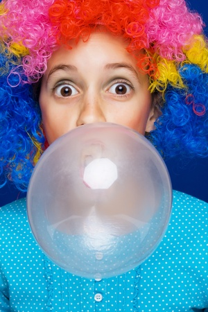 Young girl with party wig blowing bubble gum ballon