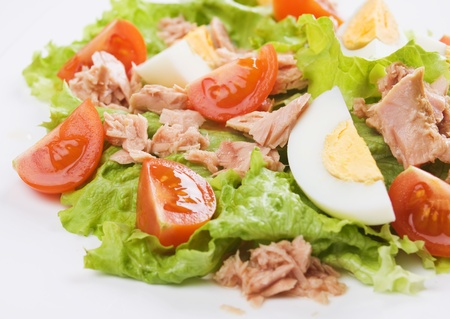 Hard boiled eggs and tuna meat salad with tomato and lettuce photo