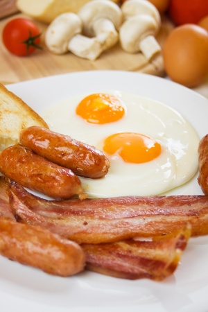 english breakfast: Fried eggs with sausage and bacon,traditional english breakfast food
