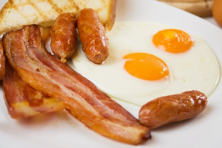 Fried bacon, sausage and eggs, traditional english breakfast food Stock Photo