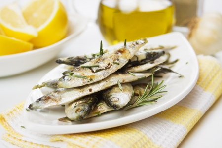 Grilled sardine fish served with lemon and rosemary Stock Photo