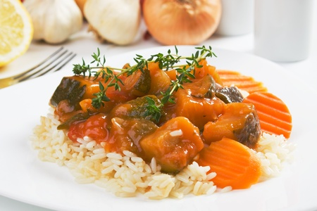 Zucchini and other vegetables in sauce served over cooked rice photo
