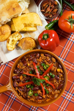 Mexican chili con carne served with peppers and corn bread