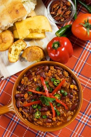 Mexikanische Chili Con Carne serviert mit Paprika und Maisbrot Standard-Bild