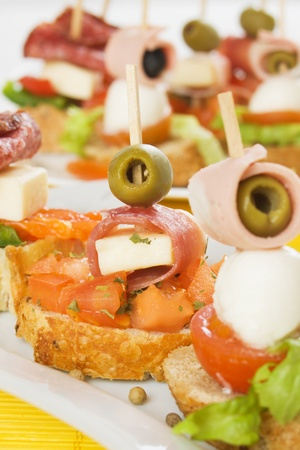 finger food: Italian bruschetta bread with ham, cheese, tomato and olives Stock Photo