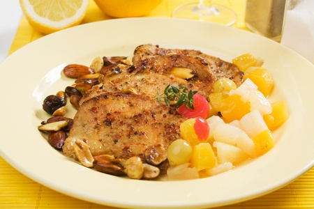 loin chops: Pork loin chops with roasted nuts and tropical fruit