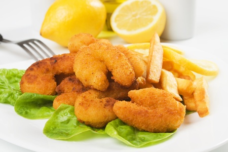 Breaded shrimp snack served with french fries and lettuce photo